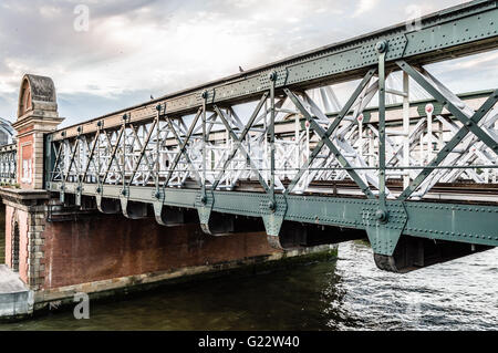 Hungerford railway bridge in London over Thames River a cloudy day - Stock Photo