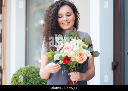 Smiling cute young woman florist with flower bouquet standing in front of shop - Stock Photo