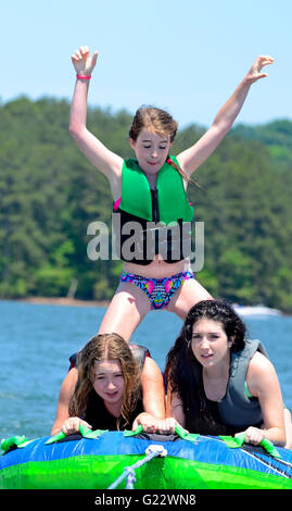 Three girls tubing behind a boat on a lake.  One is standing. - Stock Photo