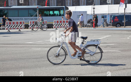 A visiting boy in a speedy start on a Gobike electric motor assisted city bike in the Copenhagen streets at Christiansborg. - Stock Photo