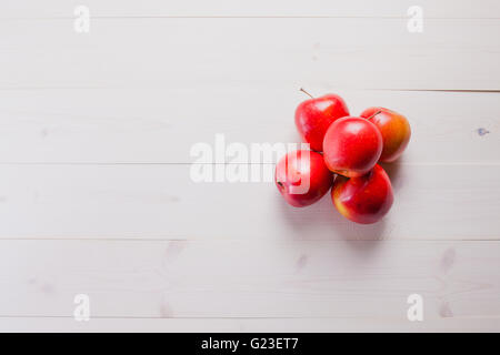 red apples on a white wood table - Stock Photo