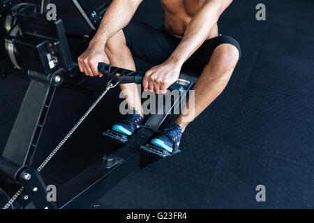 Cropped image of a muscular fitness man using rowing machine in the gym - Stock Photo