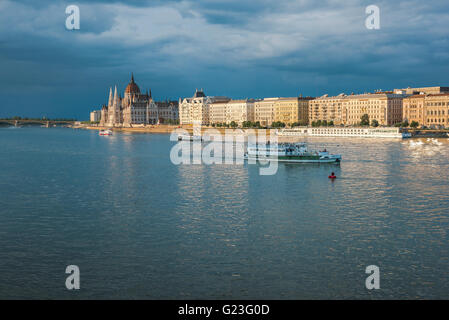 The south embankment (the Pest side) of the Danube River in Budapest illuminated at sunset, with the Hungarian Parliament - Stock Photo