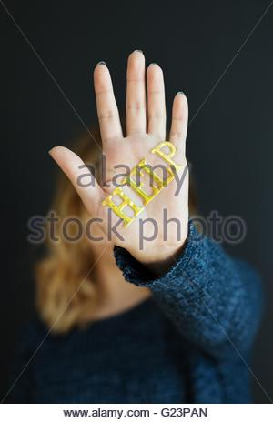 A girl with the word 'help' written on her hand which is shielding her face. - Stock Photo