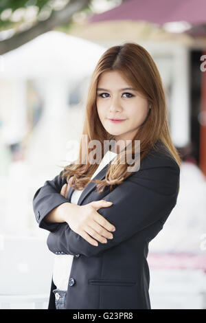asia business woman with arms crossed standing in the her office - Stock Photo