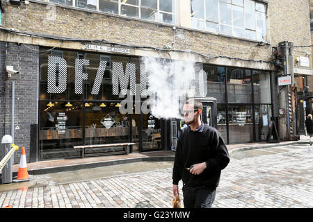 Man vaping walking by DF/Mexico Mexican restaurant on Dray Walk & Hanbury Street near Brick Lane in East London - Stock Photo