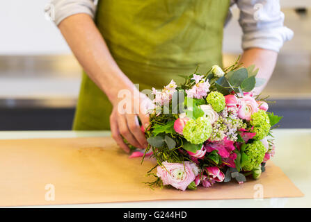 florist wrapping flowers in paper at flower shop - Stock Photo