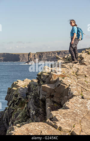 Walker at cliff edge on the Loop Head section of coast, County Clare, Ireland - Stock Photo