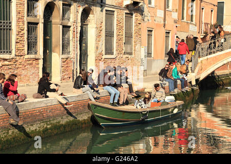 Young people enjoying a sunny day at a canal in Venice in Spring - Stock Photo