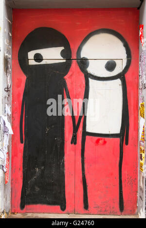 England London East End graffiti Muslim woman man holding hands by renown street artist Stix ? Princelet Street - Stock Photo