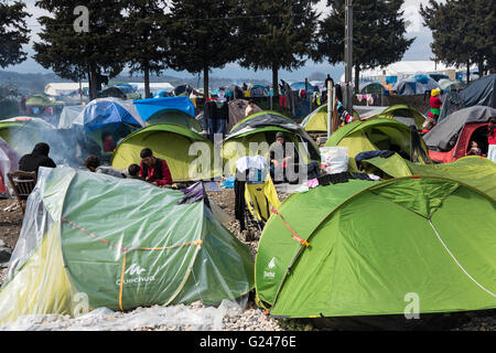 Refugees from Syria sit by their tents on March 17, 2015 in the refugee camp of Idomeni, Greece. - Stock Photo