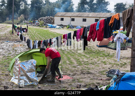 A refugee from Syria cleans his tent after heavy rain on March 17, 2015 in the refugee camp of Idomeni, Greece. - Stock Photo