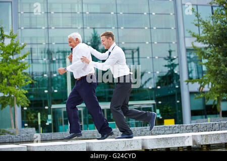 Two happy businesspeople jogging together in city in front of an office building - Stock Photo