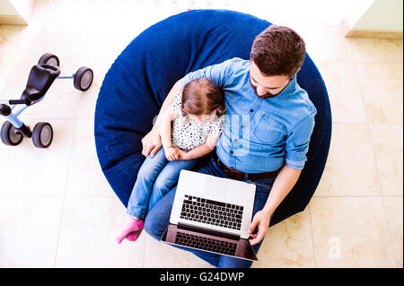 Father and daughter, playing on laptop, sitting on beanbag - Stock Photo