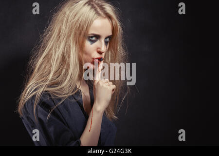 Young Woman Gesturing For Being Quiet, Shows Silence Sign In Dark Background With Copyspace - Stock Photo
