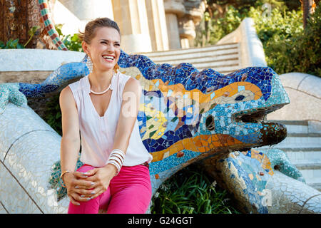 Get inspired by Park Guell in your next trip to Barcelona, Spain. Portrait of smiling young woman sitting near multicolored - Stock Photo