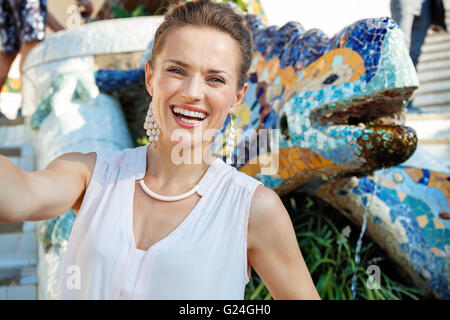 Get inspired by Park Guell in your next trip to Barcelona, Spain. Smiling young woman taking selfie near multicoloured - Stock Photo
