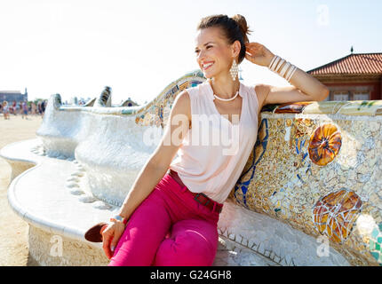 Get inspired by Park Guell in your next trip to Barcelona, Spain. Happy young woman sitting on the famous trencadis - Stock Photo