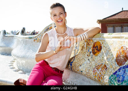 Get inspired by Park Guell in your next trip to Barcelona, Spain. Happy young woman showing heart shaped hands while - Stock Photo
