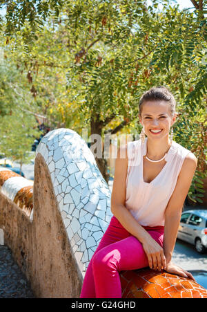 Get inspired by Park Guell in your next trip to Barcelona, Spain. Portrait of happy young woman sitting on trencadis - Stock Photo