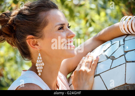 Get inspired by Park Guell in your next trip to Barcelona, Spain. Portrait of happy young woman in Park Guell - Stock Photo