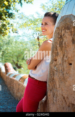 Get inspired by Park Guell in your next trip to Barcelona, Spain. Happy young woman spending time in Park Guell - Stock Photo