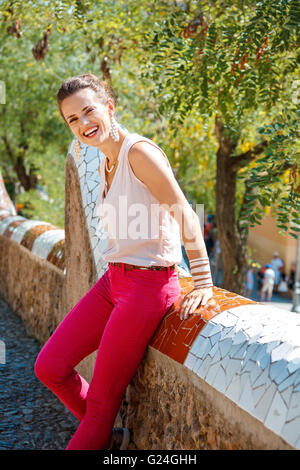 Get inspired by Park Guell in your next trip to Barcelona, Spain. Portrait of smiling young woman sitting on trencadis - Stock Photo