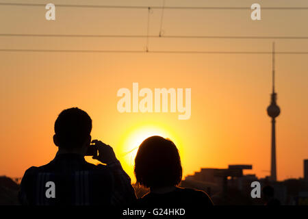 couple taking picture of sunset sky and tv tower - Stock Photo