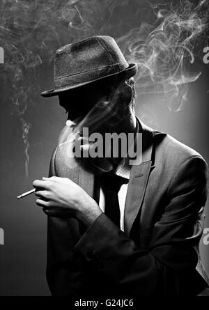 Black and white portrait of a man smoking a cigar - Stock Photo