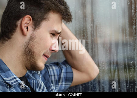 Side view of a sad man looking through window almost crying in a rainy day - Stock Photo