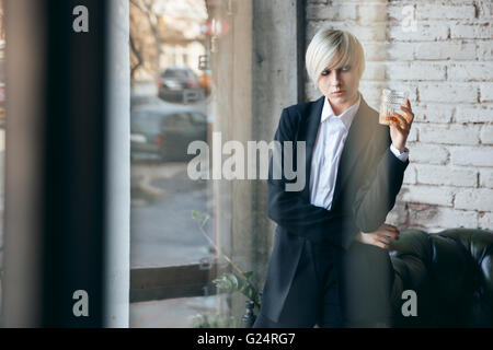 Short haired blonde girl holding a glass of whiskey in a bar - Stock Photo