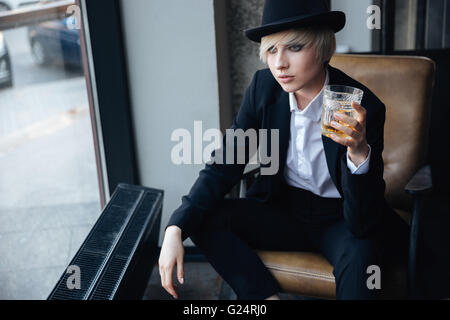 Stylish blonde girl in hat holding glass of whiskey and sitting in chair in bar looking at the window - Stock Photo