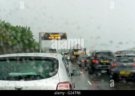 Traffic queue in the rain on the A20 approaching the junction with the M25. Warning sign reads Accident Slow Down. - Stock Photo