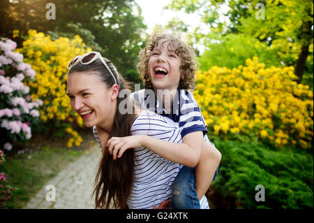 Sister carries on the shoulders of younger brother - Stock Photo