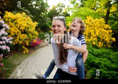 Girl playing with his younger brother in the garden - Stock Photo