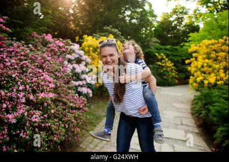 The young woman holds the boy on shoulders - Stock Photo
