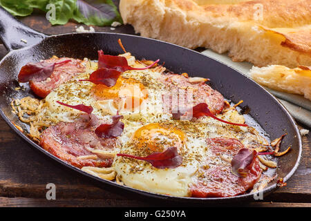 Pan of fried eggs with onion, ham and chard - Stock Photo