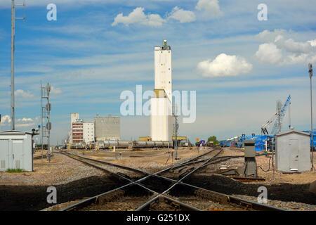 Railroad Crossing with Distant Grain Elevator Silo - Stock Photo