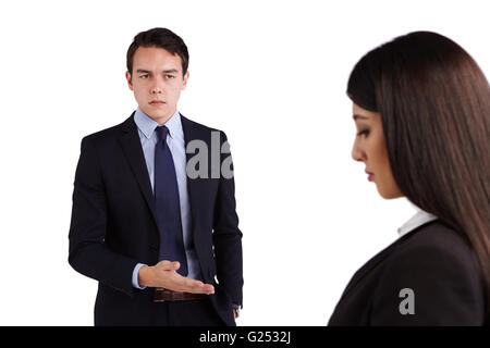 A young Caucasian man is reprimanding a business woman. He is frowining and looking angry. - Stock Photo