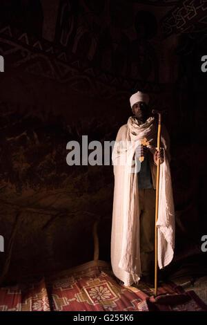 Orthodox Priest inside rock hewn church Gheralta, Ethiopia - Stock Photo