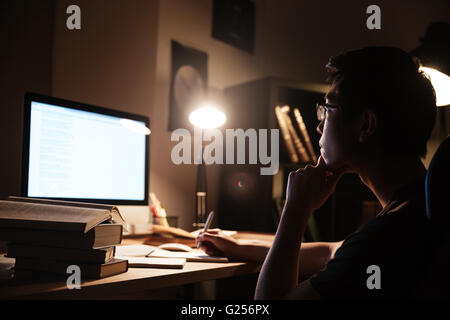 Pensive asian young man in glasses writing and working with computer in dark room - Stock Photo