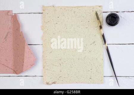 Top view of blank yellow paper, quill pen and ink on white deck table with quill pen - Stock Photo