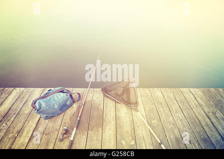 Retro stylized fishing equipment on a wooden pier. - Stock Photo