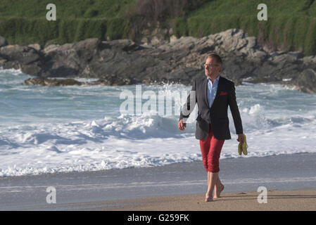 An elegantly dressed man takes an evening strolls along Fistral Beach in Newquay, Cornwall. - Stock Photo