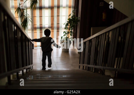 Boy walking down stairs - Stock Photo