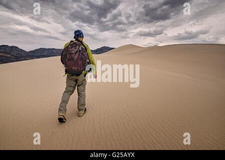 Man walking across Eureka Sand Dunes, Death Valley National Park, California, America, USA - Stock Photo