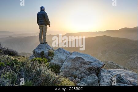 Man standing on top of mountain, McCain Valley, California, America, USA - Stock Photo