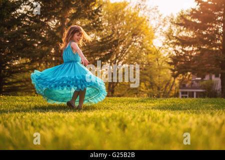 Girl in garden spinning around in a dress