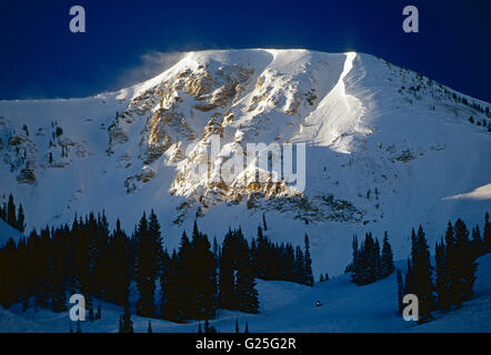 Small snowmobiler in foreground; winter view of snow covered Mount Baldy; Alta; Little Cottonwood Canyon; Utah - Stock Photo