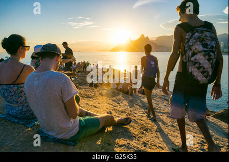 RIO DE JANEIRO - FEBRUARY 26, 2016: Crowds of people gather to watch the sunset on the rocks at Arpoador, a popular - Stock Photo